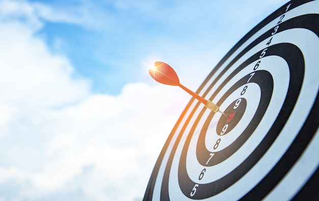 Red dart target arrow hitting on bullseye with blue sky and sunlight dreaming for target marketing and business success concept scoreboard defining clear goals