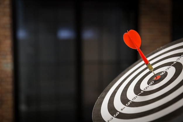 Red dart target arrow hitting on bullseye with, target marketing and business success concept - image