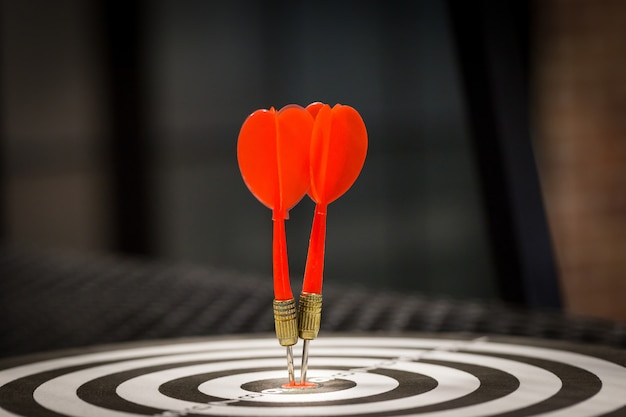 Red dart target arrow hitting on bullseye with, target marketing and business