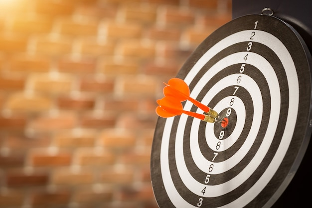 Red dart target arrow hitting on bullseye