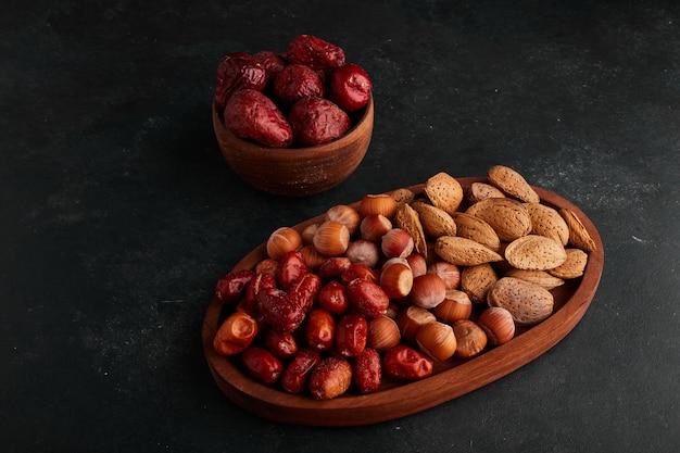 Красные финики и орехи в деревянной миске на черном пространстве.