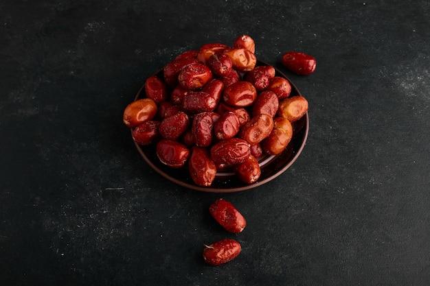 Date rosse in un piattino di ceramica sulla superficie nera.