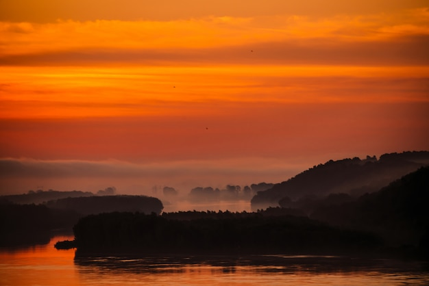 Red dawn sky reflected on water in valley of river. morning haze in distance above forest on shore. birds flying in sky at sunrise. fog on riverbank.