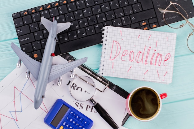 Красные слова «крайний срок» на ноутбуке с канцелярскими принадлежностями и игрушечным самолетиком. плоская композиция на синем фоне.