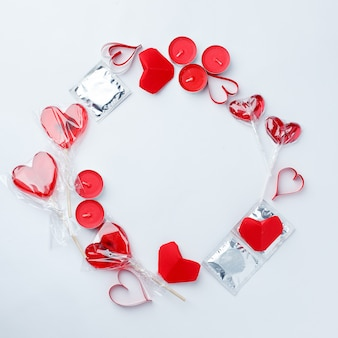 Red decor, sweetness, red heart, condoms on white background.