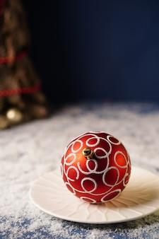 크리스마스 트리가 있는 파란색 배경에 흰색 접시에 크리스마스 트리를 위한 빨간색 장식