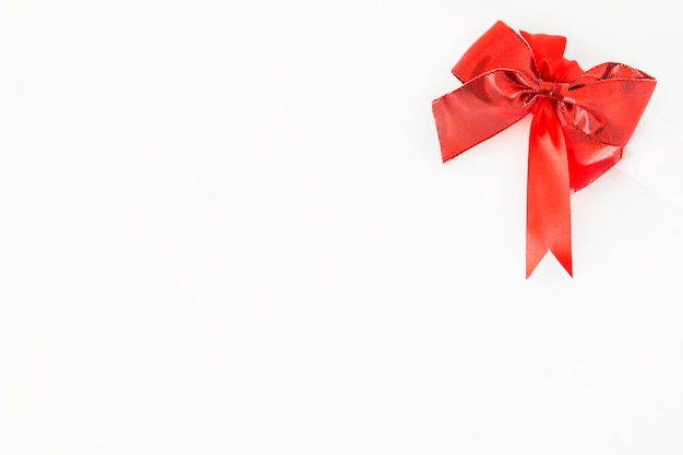 Red decorative bow on the corner of white background