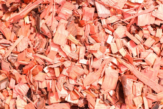 Red decorative chips, wood textured background top view. shredded tree bark for decorating a garden plot and other surfaces, close-up