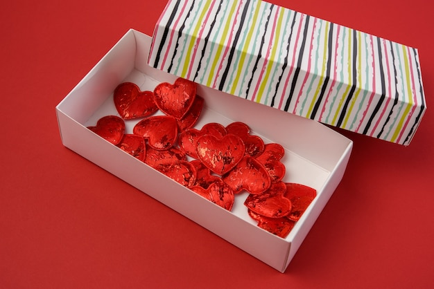 Red decorative hearts in paper box on red background, top view
