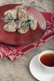 Red of delicious dried persimmon fruits and cup of tea on stone surface