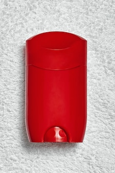 Red deo stick deodorant on a white towel, top view