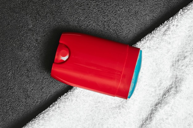 A red deo stick deodorant with blue gel lies on white towel, top view
