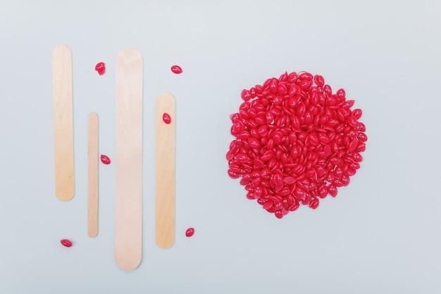 Красные гранулы воска для депиляции и шпатели для депиляции на синем фоне