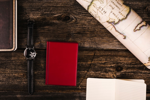 Red diary, map, and wrist watch on wooden background