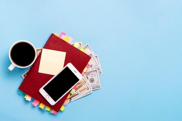 Красный дневник с наклейками на страницах, чашка с черным кофе, сто долларов, белый телефон, синий фон. концепция успешного бизнеса, правильное планирование, управление временем. плоская планировка, вид сверху