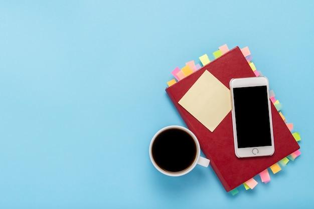 Красный дневник с наклейками на страницах, чашка с черным кофе, белый телефон, синий фон. концепция успешного бизнеса, правильное планирование, управление временем. плоская планировка, вид сверху