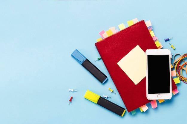 Красный дневник с наклейками на страницах, сто долларов банкноты, канцтовары, белый телефон, синий фон. с