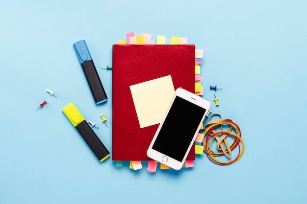 Красный дневник с наклейками на страницах, сто долларов банкноты, канцтовары, белый телефон, синий фон. концепция успешного бизнеса, правильное планирование, управление временем. плоская планировка, вид сверху