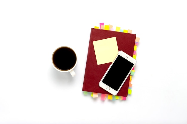 Red diary with stickers on the pages, a cup with black coffee, telephone, white background. concept of a successful business, a lot of meetings and plans for a long period. flat lay, top view