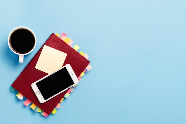 Red diary with stickers on the pages, a cup with black coffee, white phone, blue background. concept of a successful business, proper planning, time management. flat lay, top view