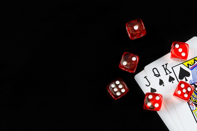 Red dice are put on for the king queen jack of spades playing card in a dark black