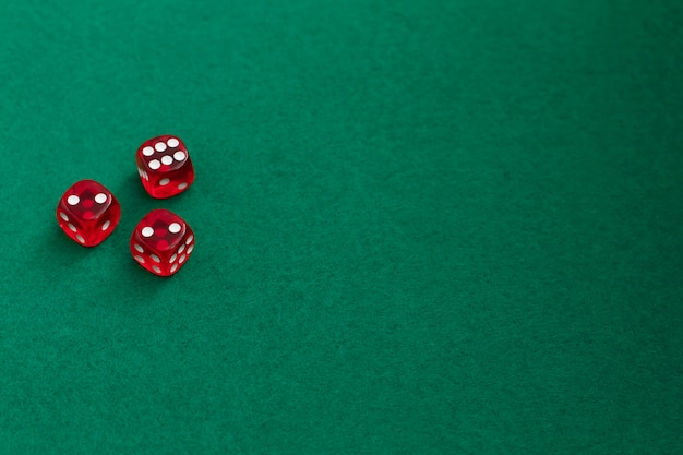 Red dice on green and black background.