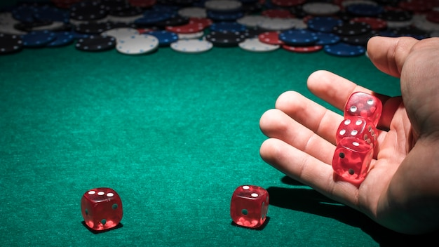 Red dice on human hand in casino