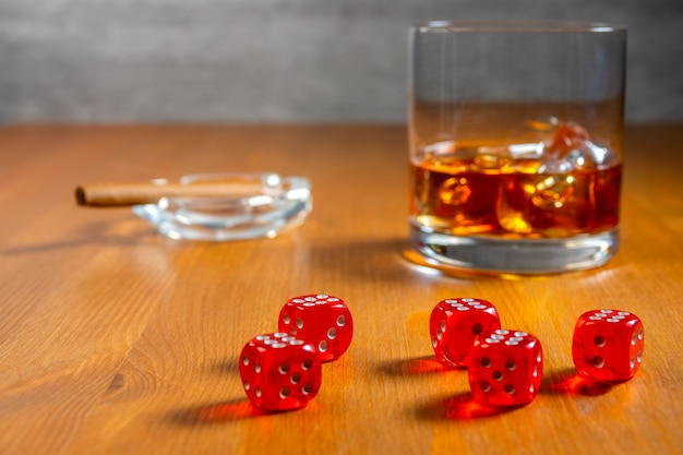 나무 테이블에 빨간 주사위입니다. 얼음 조각이 든 위스키와 시가가 든 재떨이