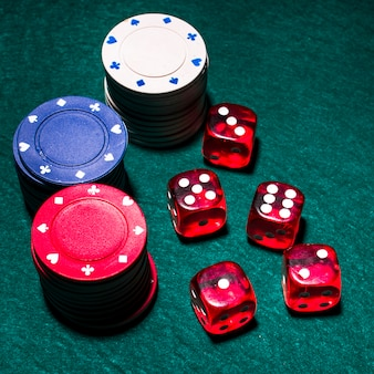 Red dices and casino chip stacks on green poker table