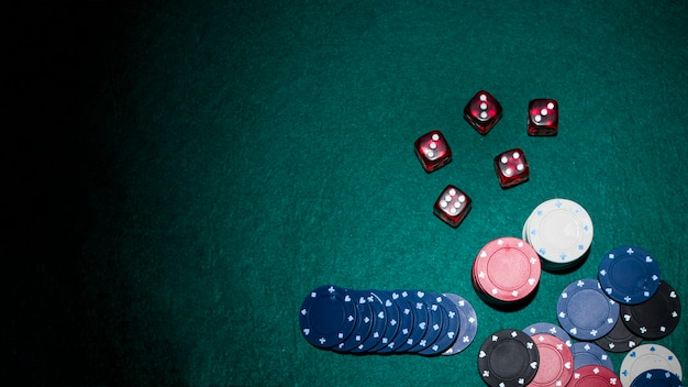 Red dices and casino chips on green poker table