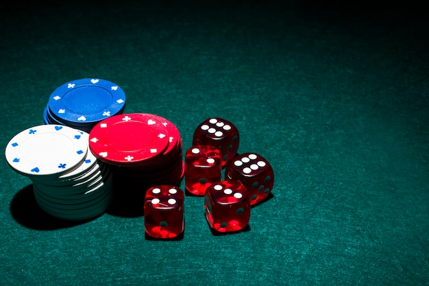 Red dices and casino chips stack on green poker table
