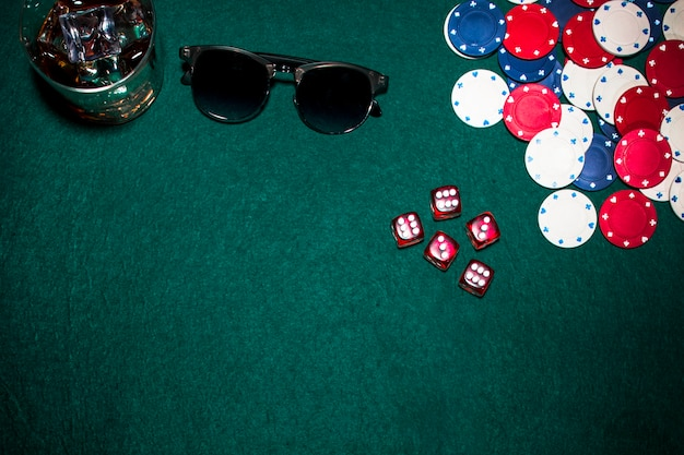 Red dices; casino chips; whisky glasses and sunglasses on green poker background
