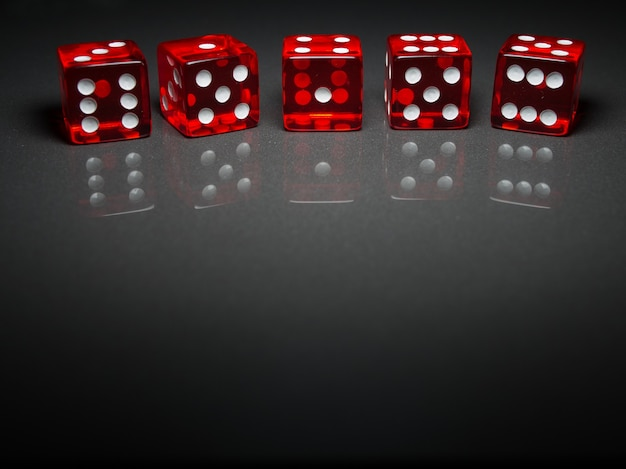 Red dices on a gray background close up