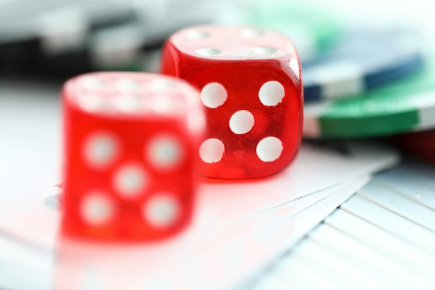 Красные кубики, лежащие с фишками казино, как символ азартных игр крупным планом