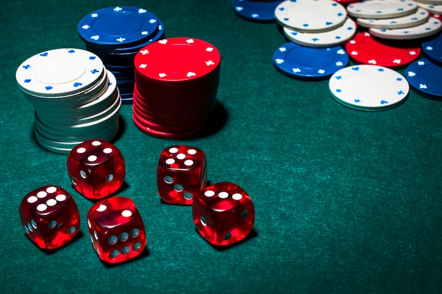 Red dices and stack of gambling chips on green poker table