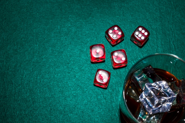 Red dices and whiskey glass with ice cubes on poker table