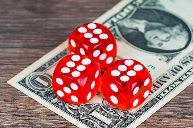 Красные кубики с банкнотой в один доллар на деревянном столе