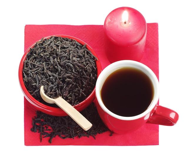 Красные блюда с черным чаем и горящей свечой, изолированные на белом