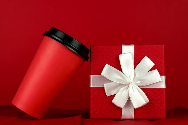 Red disposable coffe cup and gidt box on red room
