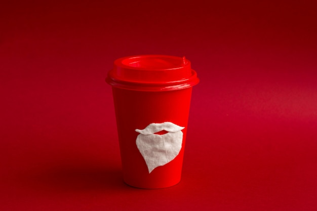Red disposable paper cup for takeaway drinks with cotton mustache and beard of santa claus
