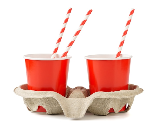 Красные одноразовые бумажные стаканчики с подставкой для стаканов и соломкой. изолированные на белом.