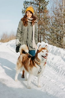 Red dog husky with his mistress brunette girl in the forest outdoors in cold season