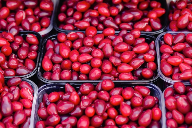 Red dogwood berries in plastic transparent container box on a street grocery shelves. dogwood crop on sale. fresh berries.