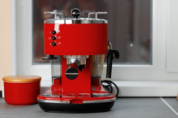 Red domestic coffee machine on kitchen counter near window