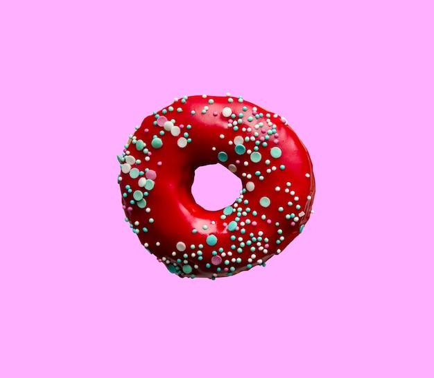 Красный пончик с начинкой из теста, изолированные на розовом фоне