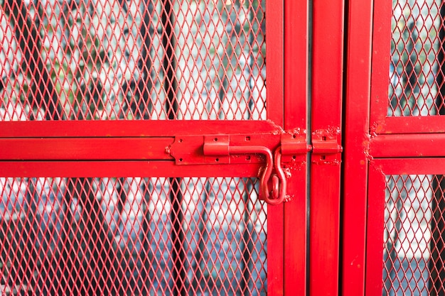 Красный дверной болт на красной железной сетке