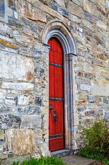 The red door to the medieval stone church