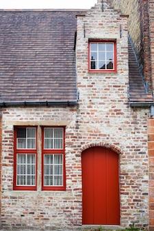 Red door on old european stone house of bruges, belgium