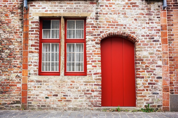 Red door and window on old european stone house of bruges, belgium