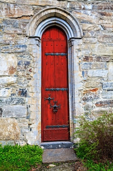 Red door with carved stone elements in the frame